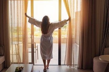Young woman wearing white bathrobe opening curtains in luxury hotel room