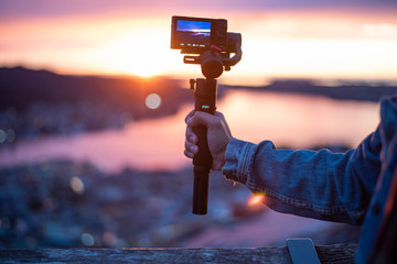 Fotobehang Aubergine Camera on stabilizer is recording beautiful view at twilight