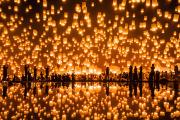 Fototapeta Thai people release sky floating lanterns or lamp to worship Buddha's relics with reflection. Traditional festival in Chiang mai, Thailand. Loy krathong and Yi Peng Lanna ceremony. Celebration. obraz