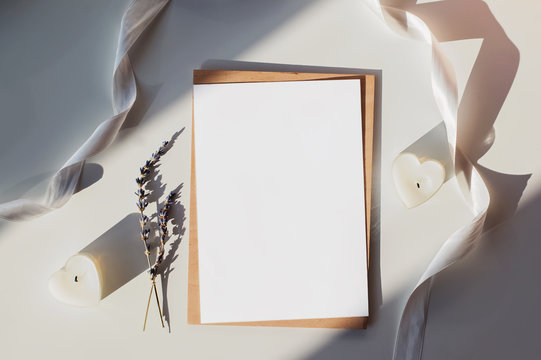 Blank paper mock-up on the table with white ribbon, lavender and heart shaped candles