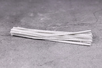 Bunch of light gray smoking pipe cleaners on concrete background