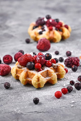 Fresh small round waffles topped with fruits like blueberry and cranberry and powdered sugar