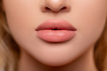 Beautiful lips Close-up. Makeup. Lip matte lipstick. Sexy lips. Part of face, young woman close up. advertisement. perfect plump lips bodily lipstick. peach color of lipstick on large lips.   Wall mural