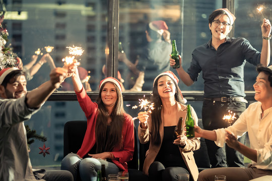 Group of diversity people having great Christmas party in working office together at night. They celebrate with beer and holding sparklers feeling happy and enjoy laughing. Xmas, new year concept