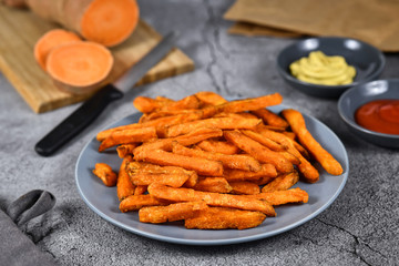 Crispy orange sweet potato fries on gray plate with whole sweet potato, ketchup and mustard dip in bacground