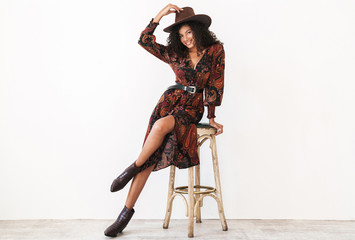 Image of african american cowgirl in dress and hat sitting on chair Wall mural