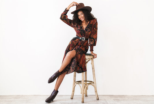 Image of african american cowgirl in dress and hat sitting on chair