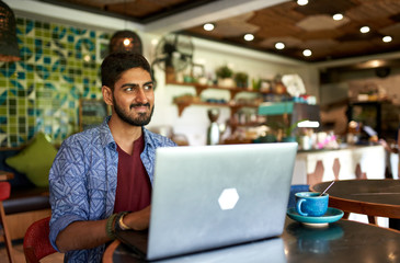 Handsome millennial indian man working in trendy coworking space Fotomurales