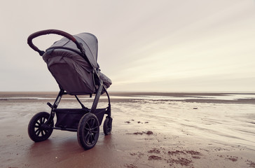 A infant baby childs stroller pushchair pram on a vast beach landscape at dusk and dawn. Relaxing and taking a holiday with children. Bonding travel with family in the great outdoors.