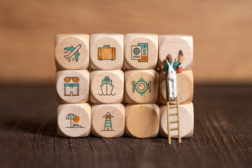 little painter figures and cubes with travel icons on wooden background