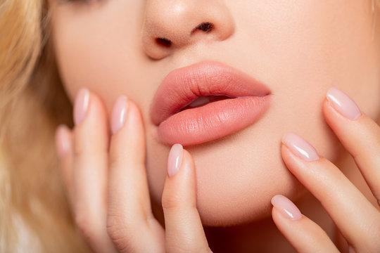 Beautiful lips Close-up. Makeup. Lip matte lipstick. Sexy lips. Part of face, young woman close up. advertisement. perfect plump lips bodily lipstick. peach color of lipstick on large lips.