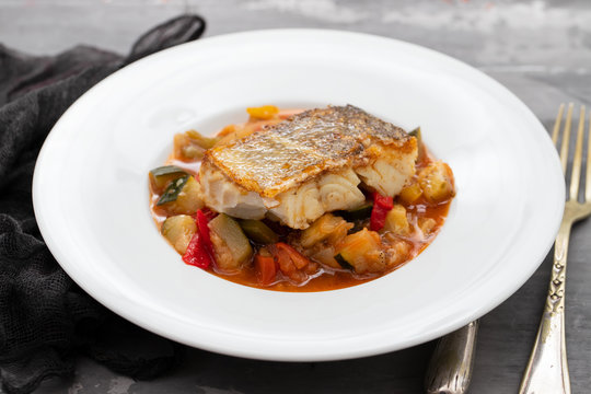 cod fish with vegetables in white plate on ceramic background