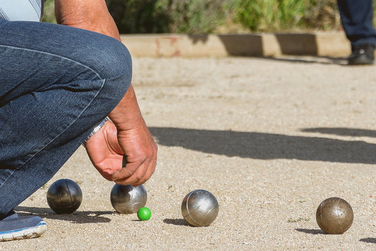Senior people playing bocce in a park