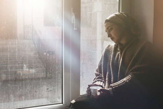 Young Muslim woman sits on window sill and looking away. Depressed middle-eastern female near the window at home. Lonely cheerless girl feeling stressed and waiting
