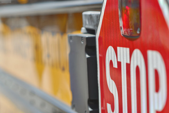 Stop sign mounted to the back of a school bus.