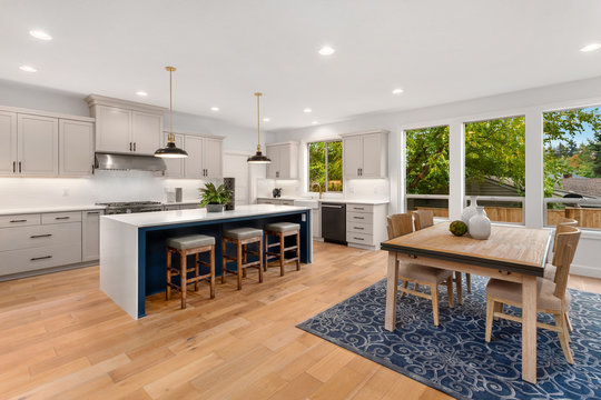 Beautiful gourmet kitchen and dining area in new luxury home with open concept floor plan. Features hardwood floors, waterfall island,  and dining room table with chairs.