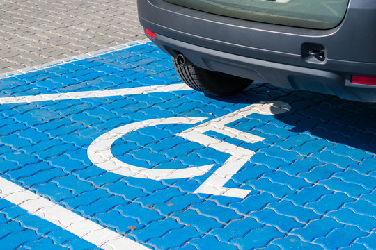 Vehicle on a fresh blue painted parking spot for people with functional impairment.  Social inequality issue.
