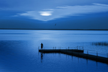 Man on pontoon pier in blue night. Color of the year 2020 Classic Blue pantone