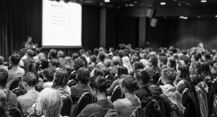 Business and entrepreneurship symposium. Speaker giving a talk at business meeting. Audience in conference hall. Rear view of unrecognized participant in audience. Black and white.
