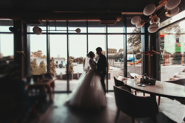 Stylish groom and beautiful bride stand near a large window. Silhouette, photography and concept, profile.