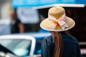 rear view woman wearing a jeans jacket and Sun Hat with Wide Brim as she looks at cars during outdoor antique car show, back selective focus.
