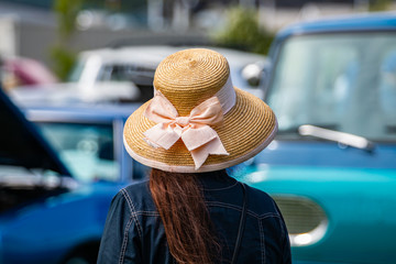 rear view woman wearing a jeans jacket and Sun Hat with Wide Brim as she looks at cars during the outdoor antique car show, blurred cars background