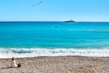 A woman sits on the beach at Menton, France on the French Riviera as a small boat and larger boat cross in front and a seagull flies above