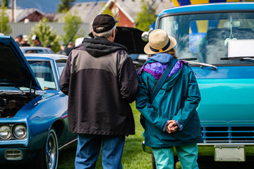 a rear view of an old couple watching classic cars, during an outdoor antique car show, sports muscle, and blue van cars in the front of them
