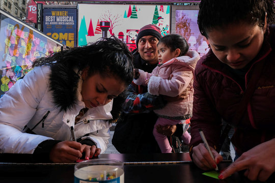 A family of tourists write down their New Year wishes on post-it notes in Times Square