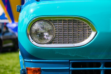 Turquoise blue old classic antique American car half front, left side, close up and selective focus on glass headlight with metallic chrome frame