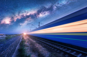 High speed train in motion and Milky Way at starry night. Industrial landscape with sky and stars over blurred modern passenger train and railroad. Railway station and space. Technology and nature Fotomurales