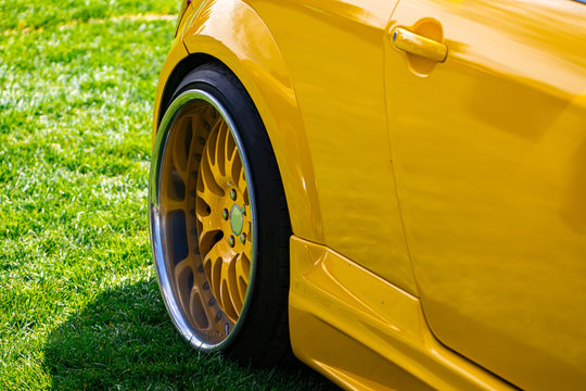 close up on yellow sports car rear wheel on grass, coupe small car with tuning is the modification, wheel with a large chrome rim and yellow interior