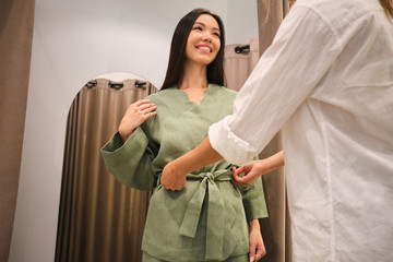 Close up fashion consultant helping trying on stylish suit to pretty smiling Asian girl in dressing room of store Wall mural