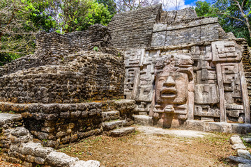 Old ancient stone Mayan pre-columbian civilization pyramid with carved face and ornament hidden in the forest, Lamanai archeological site, Orange Walk District, Belize