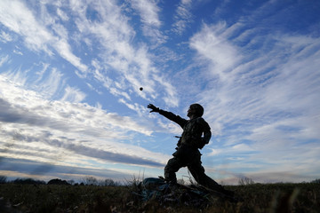 A U.S. Army soldier assigned to 101st Airborne Division (Air Assault) throws a practice hand grenade during Expert Infantryman Badge training at Fort Campbell