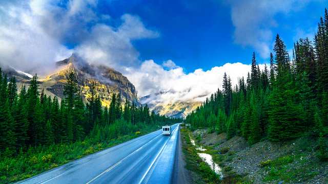 RV Motorhome Trailer Driving Into Beautiful Rain Forest Mountain Scenic Landscape