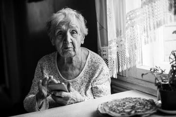 Old woman sits with a smartphone in her hands.