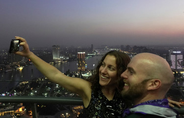Tourists take a selfie mobile picture at a view of the city skyline and the River Nile from Cairo tower building in the capital of Cairo