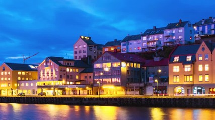 Wall Mural - Kristiansund, Norway. View of city center of Kristiansund, Norway during the cloudy night with colorful sky. Time-lapse of port with historical buildings, panning video