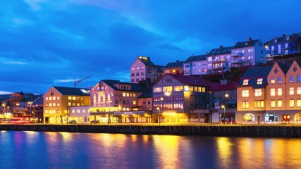 Wall Mural - Kristiansund, Norway. View of city center of Kristiansund, Norway during the cloudy night with colorful sky. Time-lapse of port with historical buildings, zoom in