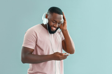 African-American man listening to music on color background