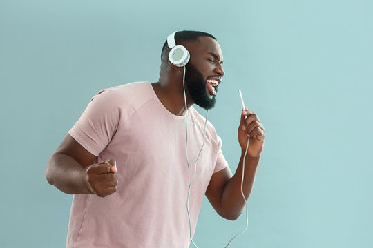 African-American man listening to music and singing on color background