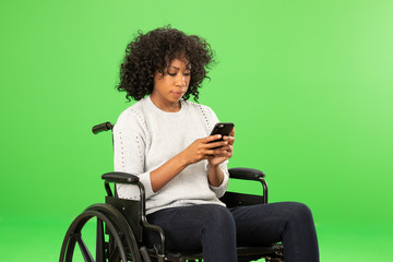 Young black woman sitting in wheelchair using smartphone