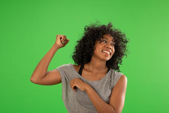 A beautiful happy African American female dancing on greenscreen