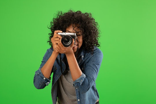 Portrait of happy black female photographer taking a photo on greenscreen