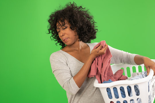 African American woman disgusted by smelly laundry on greenscreen