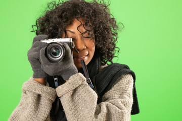 Female photographer wearing scarf and sweater taking photo on green screen