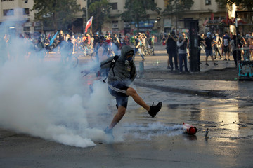 A protester kicks a canister of tear gas during a protest against Chile's government in Santiago