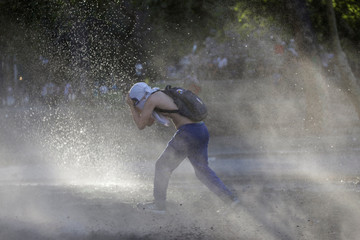 A protester covers his face as a water cannon is sprayed during a protest against Chile's government in Santiago