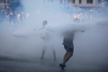 Protesters react as a water cannon is sprayed during a protest against Chile's government in Santiago